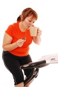 woman-drinking-coffee-on-exercise-bike
